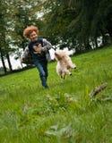 孩子和狗赛跑 库存照片