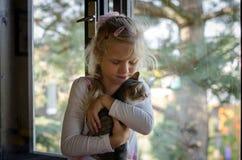 孩子和猫在窗口旁边 免版税库存照片