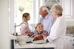 孩子和祖父母在厨房里做烘烤土耳其膳食 图库摄影