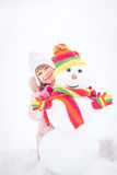 孩子和雪人在冬天 免版税图库摄影