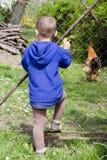 孩子和鸡在农场 免版税图库摄影