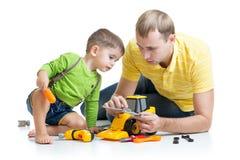 孩子和他的爸爸修理玩具拖拉机 免版税库存图片