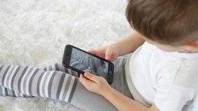 孩子喜欢使用与在白色背景的一个电话,拍摄他的腿 特写镜头 股票录像