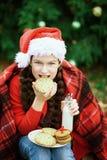 孩子喝从瓶的牛奶和吃曲奇饼 等待在木头的微笑女孩圣诞节 免版税图库摄影