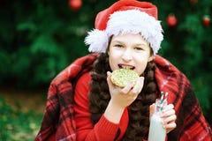 孩子喝从瓶的牛奶和吃曲奇饼 等待在木头的微笑女孩圣诞节 免版税库存照片