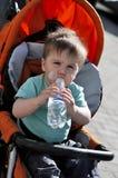 孩子喝从一个瓶的水在stoller 免版税库存图片
