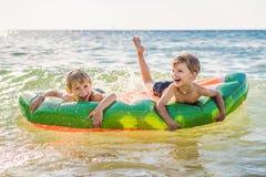 孩子在一个可膨胀的床垫的海游泳和获得乐趣 免版税库存图片