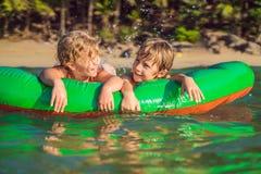孩子在一个可膨胀的床垫的海游泳和获得乐趣 库存图片