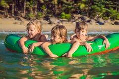 孩子在一个可膨胀的床垫的海游泳和获得乐趣 图库摄影