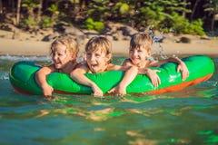 孩子在一个可膨胀的床垫的海游泳和获得乐趣 免版税库存照片