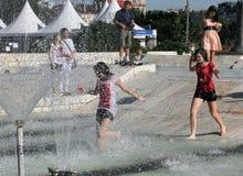 """孩子在一个喷泉的水中使用在一个晴朗的夏日在暑假期间在索非亚,保加利亚†""""2012年6月15日 晴朗的天气c 免版税图库摄影"""