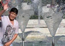 """孩子在一个喷泉的水中使用在一个晴朗的夏日在暑假期间在索非亚,保加利亚†""""2012年6月15日 晴朗的天气c 免版税库存图片"""