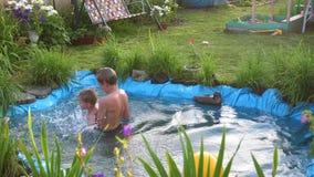 孩子在一个小湖游泳在一个热的夏日 庭院、花和植物在湖附近 愉快的童年 股票录像
