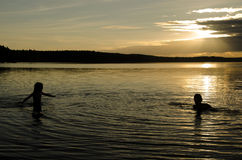 孩子在一个湖的水中日落的 免版税库存照片