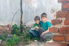 孩子在一个被放弃的房子里,两个可怜的被抛弃的男孩、孤儿由于自然灾害和军事行动 ?? 免版税图库摄影