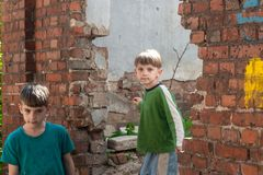 孩子在一个被放弃的房子里,两个可怜的被抛弃的男孩、孤儿由于自然灾害和军事行动 ?? 库存图片