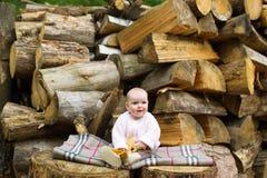 孩子在一套日志中坐 免版税图库摄影