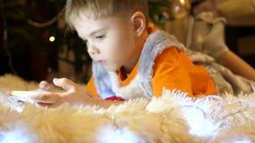 孩子在一条软的白色毯子说谎在儿童房间 他观看在智能手机的动画片 圣诞节 股票录像