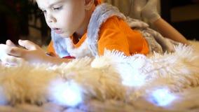 孩子在一条软的白色毯子说谎在儿童房间 他观看在智能手机的动画片 圣诞节 股票视频