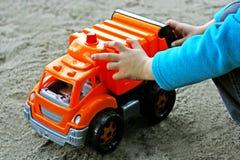 孩子在一辆大玩具汽车附近坐 库存图片