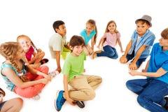 孩子在与一个男孩的圈子坐在中心 图库摄影