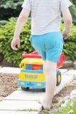 孩子在与一辆大红色玩具汽车的草使用 图库摄影