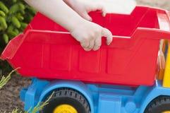 孩子在与一辆大红色玩具汽车的草使用 免版税图库摄影