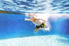 孩子在与面具的游泳池游泳 免版税图库摄影