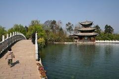 孩子在丽江过导致黑龙水池的一个亭子的桥梁 免版税库存照片