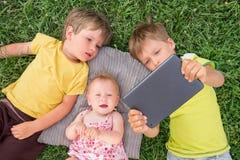 孩子在他们的说谎在草的手上拿着ipad 免版税库存图片
