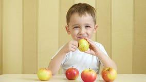 孩子在他的手上拿着一个苹果并且显示他的赞许 股票录像