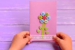 孩子在他的手上拿着一张花卡片 孩子做了妈妈或爸爸的一张贺卡 生日,母亲节,父亲节礼物想法 库存图片
