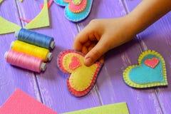 孩子在他的手上拿着毛毡心脏华伦泰 孩子做了毛毡心脏华伦泰 五颜六色的毛毡心脏,剪刀,螺纹集合 免版税库存照片