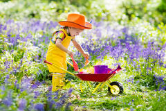 孩子在会开蓝色钟形花的草庭院里 免版税库存照片