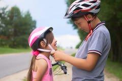 孩子在公园学会骑自行车在夏日 投入安全帽的少年男孩帮助的学龄前儿童女孩 库存照片