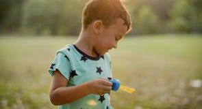 孩子在公园演奏泡影 免版税库存图片