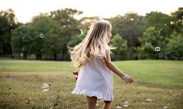 孩子在公园演奏泡影 免版税图库摄影