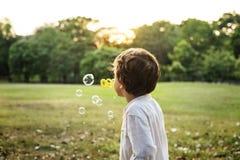 孩子在公园演奏泡影 免版税库存照片