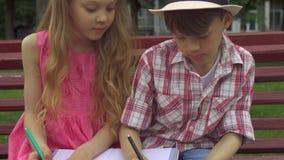 孩子在册页使一致在长凳 免版税库存照片