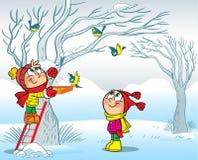 孩子在冬天喂养了鸟 免版税库存图片