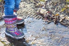 孩子在冰冷的肮脏的水坑站立 免版税图库摄影