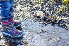 孩子在冰冷的肮脏的水坑站立 库存图片