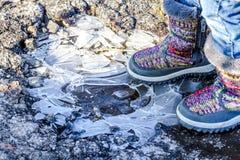 孩子在冰冷的肮脏的水坑站立 免版税库存照片