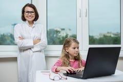 孩子在办公室坐在桌上,看膝上型计算机 以妇女医生和窗口为背景 免版税库存图片