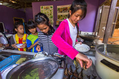 孩子在午餐时间的教室在项目柬埔语的学校哄骗关心 库存图片