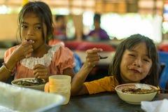 孩子在午餐时间的教室在项目柬埔语的学校哄骗关心 免版税库存图片