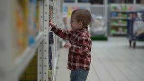 孩子在商店或超级市场买婴儿食品 库存照片