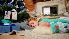孩子在圣诞树,拥抱玩偶的小逗人喜爱的女孩附近睡觉在睡眠,甜睡眠期间在客厅 股票视频