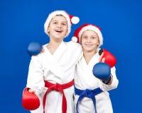 孩子在圣诞老人盖帽和在手上的红色和蓝色覆盖物 库存图片