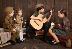 孩子在坐和弹吉他的减速火箭的军服打扮,派遣战士到军队,黑暗的木背景, r 免版税库存照片